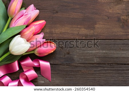 Pink and white tulips on dark wood background - stock photo