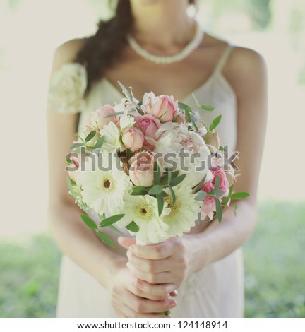 pink and white wedding bouquet of roses in the hands of the bride - stock photo