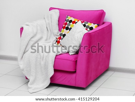 Pink armchair with blanket and pillows on light wall background - stock photo