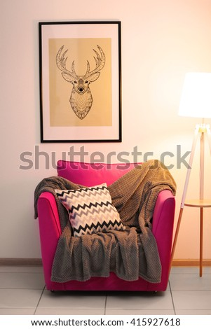 Pink armchair with blanket, pillow and lamp on light wall background - stock photo