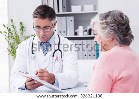 Pink awareness ribbon against doctor explaining prescriptions to senior woman - stock photo