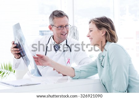 Pink awareness ribbon against doctor having conversation with his patient and holding xray - stock photo