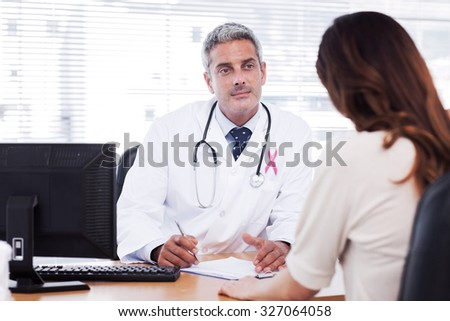 Pink awareness ribbon against doctor listening to his patient talking about her illness