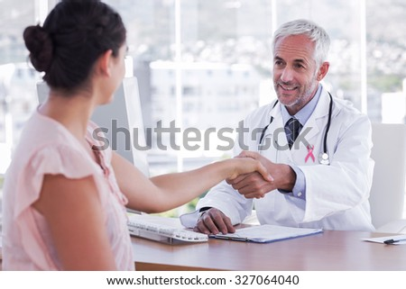 Pink awareness ribbon against doctor shaking hands to patient - stock photo