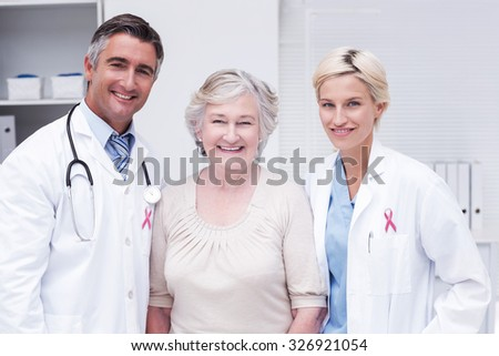 Pink awareness ribbon against doctors and senior patient smiling in clinic - stock photo