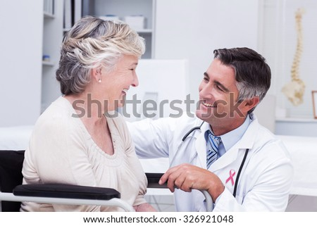 Pink awareness ribbon against male doctor looking at female patient - stock photo