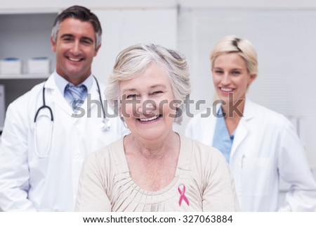 Pink awareness ribbon against senior patient smiling with doctors in clinic - stock photo
