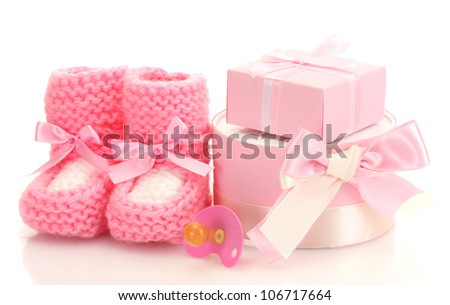 pink baby boots,  pacifier and gifts isolated on white