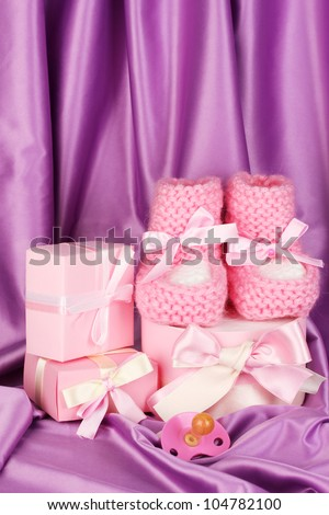 pink baby boots, pacifier, gifts on silk background - stock photo
