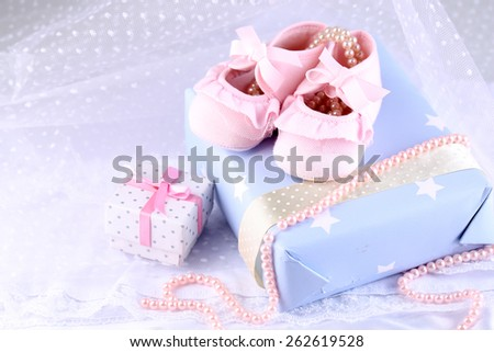 Pink baby boots with gift close-up - stock photo