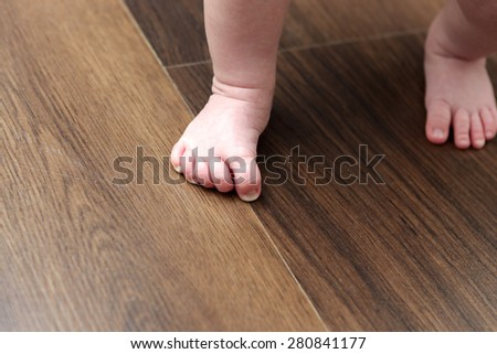 Pink baby feet on a wooden floor