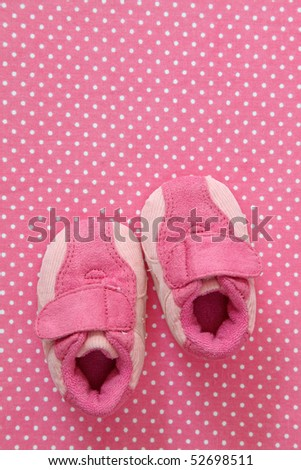 Pink baby shoes on spotted background - stock photo