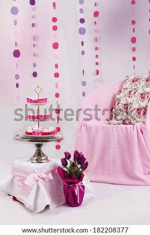 Pink baby shower decor with garland and dessert table