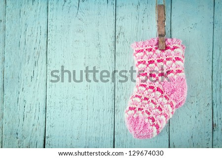 Pink baby socks on a blue wooden rustic background with copy space - stock photo