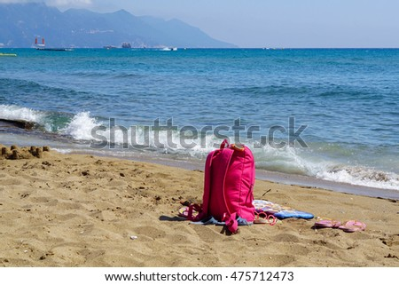 Pink backpack on the beach.