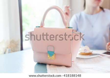 Pink bag on the table. French cafe. Beautiful girl near the window. - stock photo
