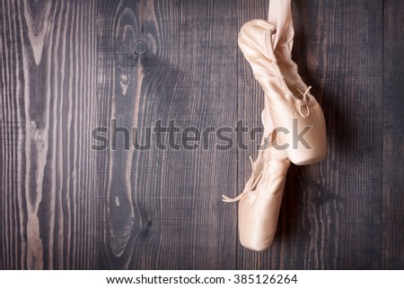 Pink ballet shoes on a wooden background - stock photo