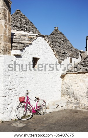 Pink bicycle against a white wall in Alberobello, Italy. - stock photo