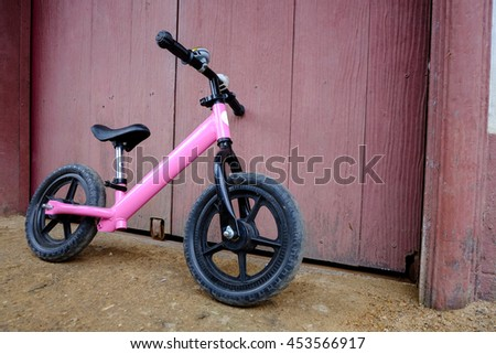 Pink bicycle leg pull,And a gold Bell with a flashing light on the handle.The background is purple door
