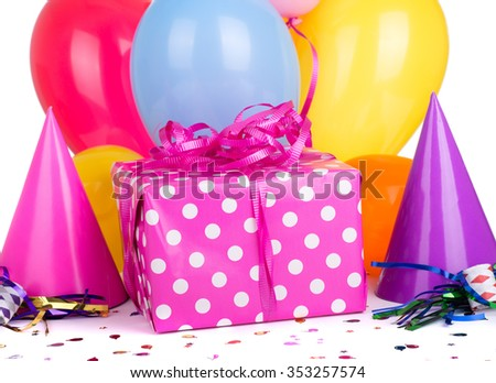 Pink birthday present and ribbon with party hats and balloons - stock photo