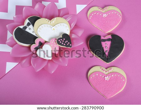 Pink, black and white wedding hearts shape cookies with bride and groom and wedding party on modern pink and white table setting. - stock photo
