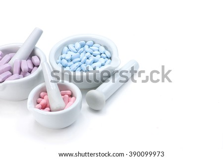 Pink, blue and purple tablets in three mortar and pestles on white background with copy space to right.
