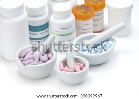 Pink, blue and purple tablets in three mortar and pestles on white background with prescription bottles. Labels are fictitious and created by photographer.
