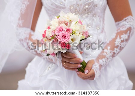 Pink bouquet in bride's hands with roses, eustoma,phalaenopsis and orchid. Horizontal closeup image - stock photo