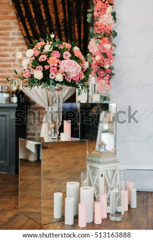 Pink bouquets and candles stand on glass boxes before wedding al