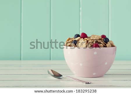 Pink bowl with cereals, raspberries and blueberries. Robin egg blue background. Vintage look. - stock photo