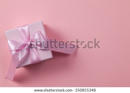 Pink box with ribbon and bow on a paper background with space for text - stock photo