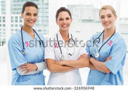 Pink breast cancer awareness ribbon against portrait of female doctors with arms crossed - stock photo
