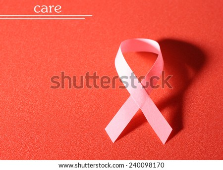 Pink breast cancer ribbon on red background - stock photo