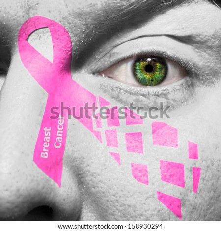 Pink breast cancer ribbon painted on a face with a green eye - stock photo