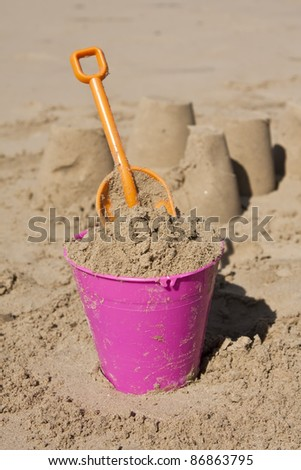 Pink bucket and orange spade in sand on the beach - stock photo