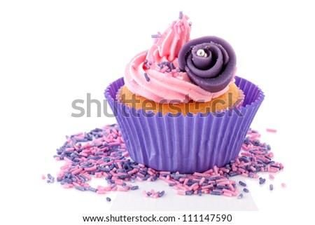 Pink butter cream on cupcake with sprinkles and purple flower