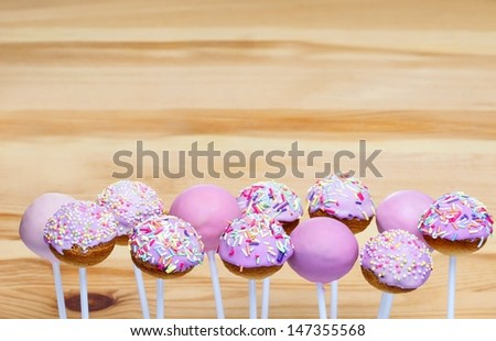 Pink cake pops on wooden background. Copy space - stock photo