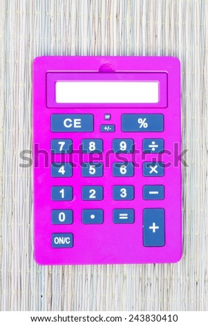 pink calculator on traditional mat with white space on the screen - stock photo