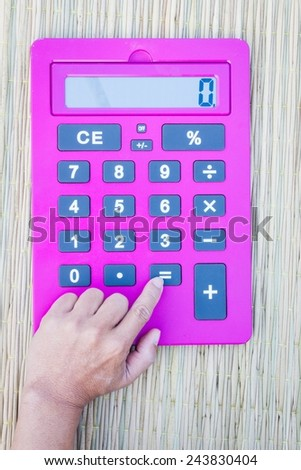 pink calculator on traditional mat with white space on the screen, hand pushing equal button - stock photo