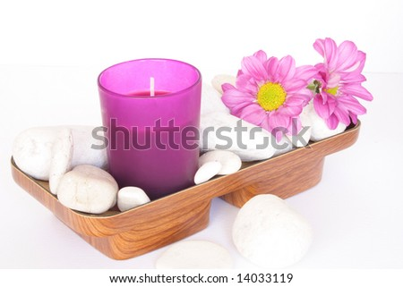 Pink candle and white pebbles with flowers - stock photo