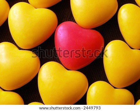 Pink candy heart surrounded by yellow hearts. - stock photo