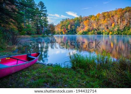 Pink canoe by colorful lake surrounded by fall colors in Smokey Mountains - stock photo
