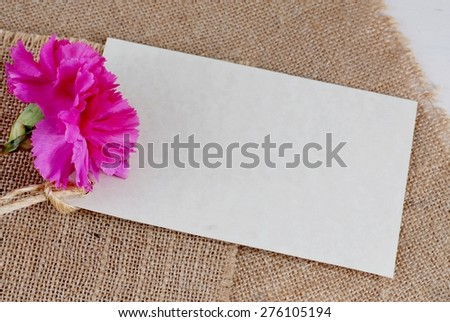 Pink carnation decorates a mottled, parchment paper style card that is blank for your message. The flower and message are on a burlap and shabby chic wooden background. Image has warm tones. - stock photo