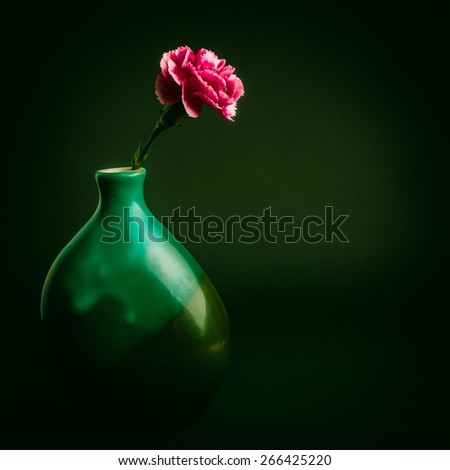 Pink carnation flower in a green vase on black background - stock photo