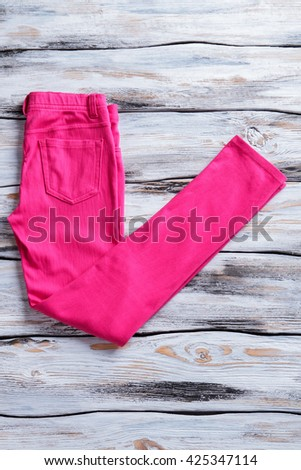 Pink casual pants. Pants on white wooden background. Regular fit pants for women. Item from new collection.