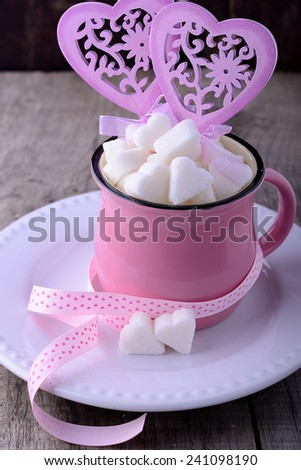 Pink ceramic mug on the wooden background full of sweet hearts for Valentine's Day. selective Focus - stock photo