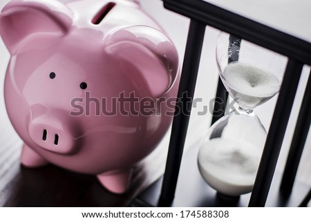 Pink ceramic piggy bank with an hour glass, conceptual of time running out to save for your retirement, a nest egg or to meet your dreams - stock photo