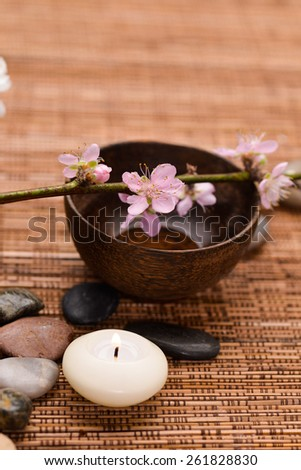 Pink cherry flower in wooden bowl with stones, candle and mat  - stock photo