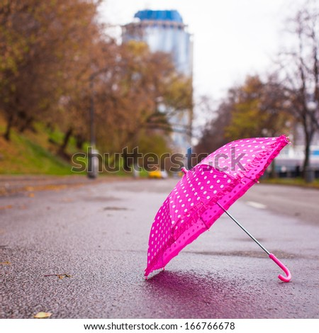 Pink children's umbrella on the wet asphalt outdoors - stock photo