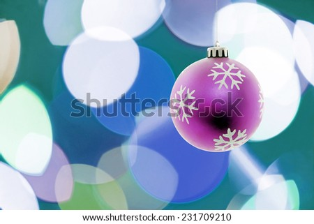 Pink Christmas ball hanging.Lights on the background.Copy space - stock photo